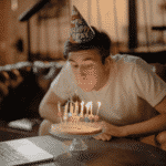 guy blowing out birthday cake candles while sitting in front of laptop