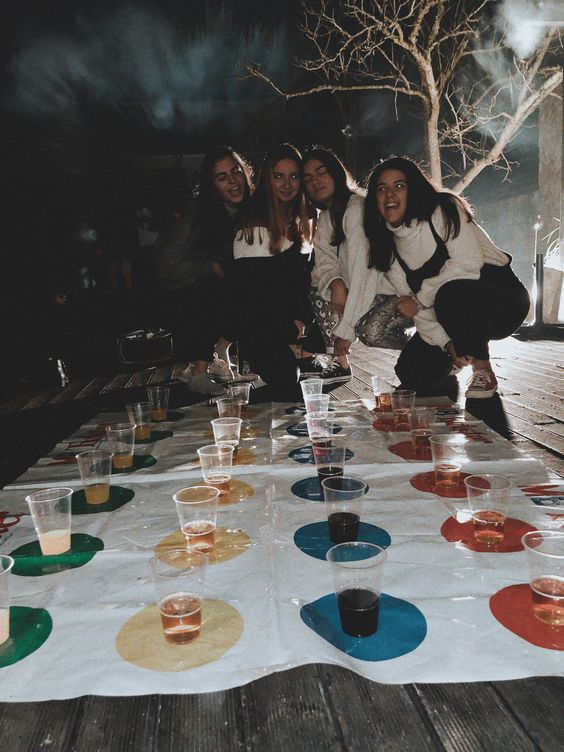 Four girls looking at the game of Twister which has alcoholic drinks on each circle