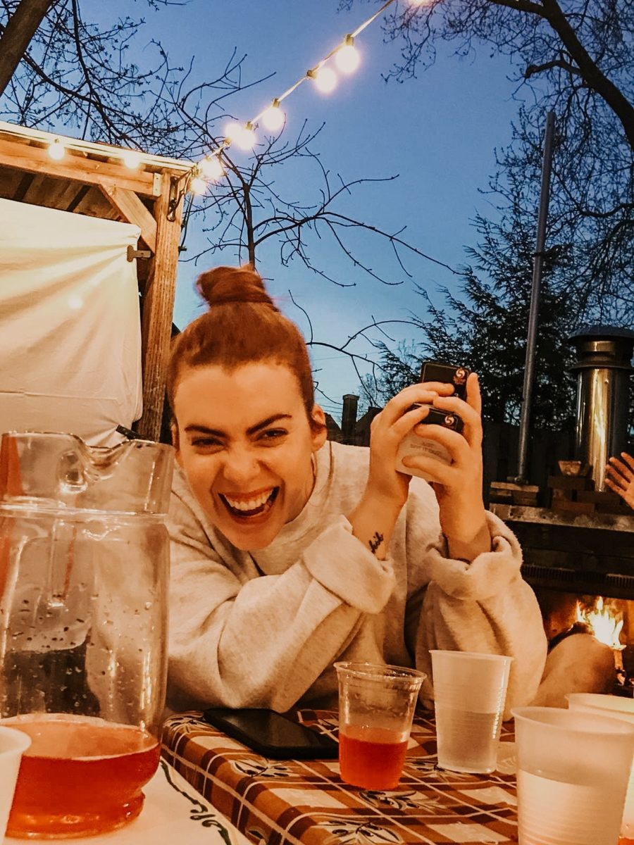 Girl outdoor sitting at table with drinks on it holding card game and laughing