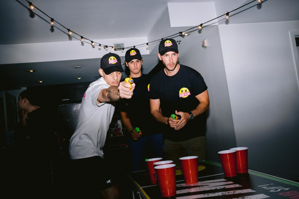 Three guys playing nerf gun game at a house party